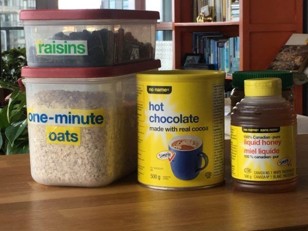 Oats in container beside can of hot chocolate and bottle of honey to show easy to read labels