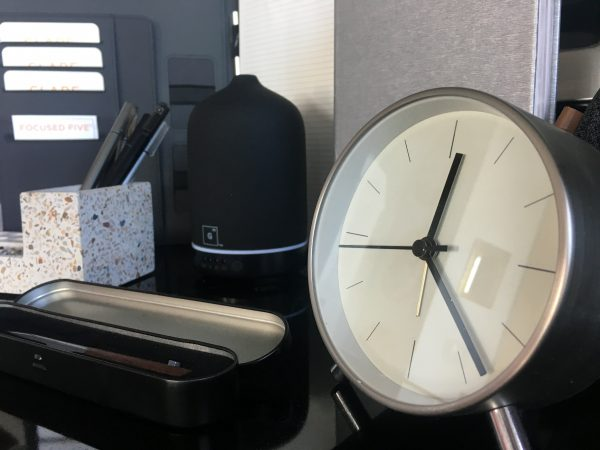 sleek desk clock in silver, beside ceramic black diffuser